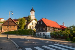 Street view of Nove Mesto nad Metuji, Czech Republic. Old manor houses and Holy Trinity Church at sunny day