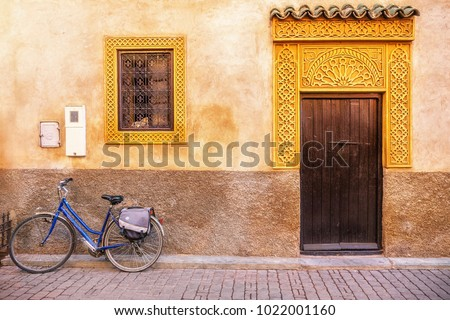 Street view of old house exterior in Morocco, with a wooden door and fancy gold colored window and door frames. A bicycle parked in front on the cobblestone street.