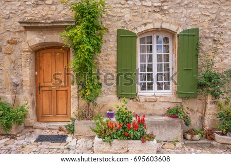 Street view of quaint French provincial house facade with wooden door, shuttered window and garden plants. Cobblestone street. Provence.