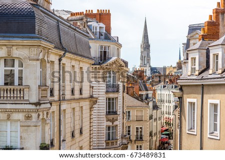 Street view on the beautiful residential buildings andchurch tower in Nantes city during the sunny day in France Photo stock ©