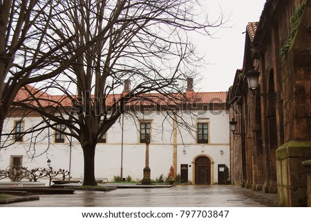 Street view with some trees and a romanic church side in Aviles. Northern Spain street landscape in a cloudy day.