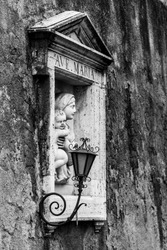 Street wall religious niche with small sculpture of Maria with Jesus. Black and white image.