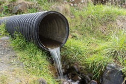 Street water drainage pipe emptying water out into nature.