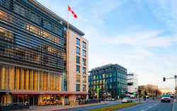 Street with modern building with Canadian flag in Potsdamer Platz Square in City centre in Berlin in Germany in Europe. Building architecture exterior.