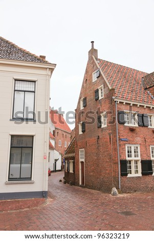 Street with old houses in dutch city Amersfoort. In winter with cloudy sky.