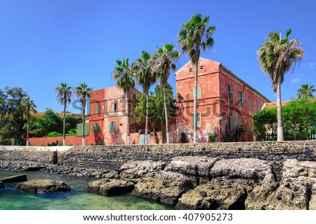 Street with old red houses at the coast of Goree island, Dakar, Senegal #407905273
