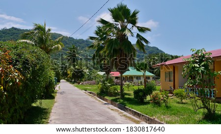 Street with palm trees and holiday homes (tourist accommodations) in village on La Digue island, Seychelles. Photo stock ©