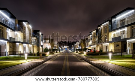 Street with townhouses in the night town. Panoramic view of district with townhouses at dusk. Panorama of illuminated houses in a small city.