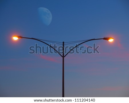 Streetlight glowing at the sunset with moon rising in the background - stock photo