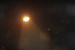 Streetlight in the dark of the night during a raining day. emitting a very orange light. Shimmer and flare effects, ideal for mysterious scene or solitude concept