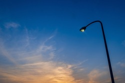 Streetlights illuminated with dusk sky