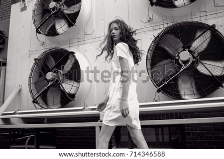 Streetstyle, fashion. Bw young girl in white dress walking on ventilation background