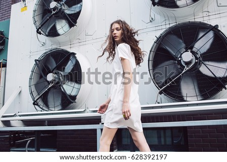 Streetstyle, fashion. Young girl in white dress walking on propellers background