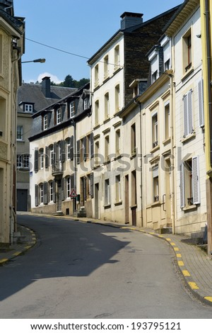 Streetview of a curved gradiented street with houses of generic Belgian architecture in Bouillon, Belgium