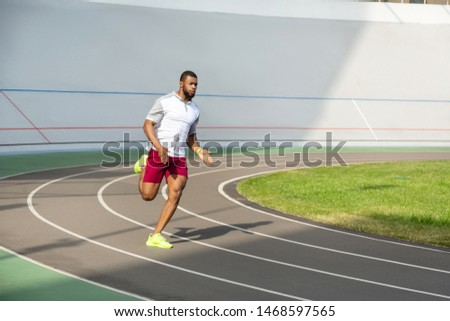 Strength and endurance. Strong purposeful sportive young man running on the running track looking in front of him