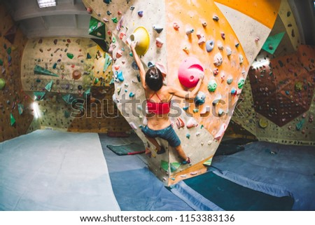Strength and endurance training. The climber trains on the climbing wall. A woman trains to climb on an artificial relief. A slender girl goes in for sports. #1153383136