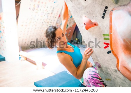 Strength and endurance training. The climber trains on the climbing wall. A woman trains to climb on an artificial relief. A slender girl goes in for sports. #1172445208