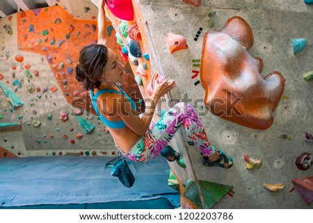 Strength and endurance training. The climber trains on the climbing wall. A woman trains to climb on an artificial relief. A slender girl goes in for sports. #1202203786