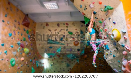 Strength and endurance training. The climber trains on the climbing wall. A woman trains to climb on an artificial relief. A slender girl goes in for sports. #1202203789