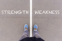 Strength and weakness text on asphalt ground, feet and shoes on floor, personal perspective footsie concept