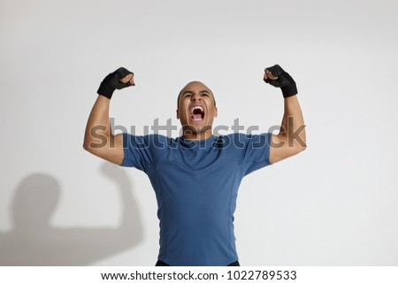 Strength, energy, power, sports and determination concept. Picture of determined young dark skinned sportsman roaring in studio, pumping fists and keeping mouth wide opened, showing his muscles #1022789533