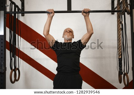 Strength, sports, energy and motivation concept. Picture of senior bearded man with strong muscular arms exercising indoors, doing pull ups. Elderly male performing pulling exercise on horizontal bar