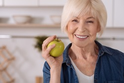 Strengthen your teeth. Close up of a cheerful elderly woman holding an apple while standing in the kitchen