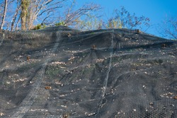 Strengthening the mountain slope with a metal mesh that prevents rockfall on the road. Abstract background of the security concept.