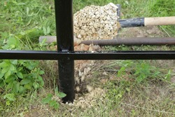 Strengthening the pillars of the base of the new metal fence with gravel, breakstone falls from the shovel