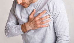Stress and health concept. Young man experiences chest pain and leans, close up, panorama, cropped