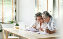 Stress Asian Senior Couple using calculator and calculate family budget, Debts, monthly expenses in home during Financial economic crisis. Elderly man, woman looking at bill, passbook, receipt, laptop