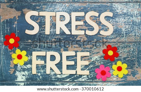 Stress free written with wooden letters on rustic wooden surface and colorful flowers