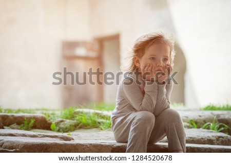 Stress kid. violence against child. Sad children. toddler girl. Toddler angry kid. concept for bullying, depression stress or frustration baby sitting alone outdoors