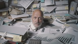 Stressed accountant working in the office, he is drowning under a lot of paperwork and overwhelmed by work
