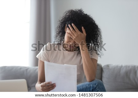 Stressed african American young woman hold paper document feel distressed with eviction notice or dismissal notification, upset black female read letter get bad news from correspondence mail #1481307506