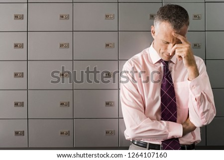 Stressed and worried businessman in front of safety deposit boxes looking down with anxiety