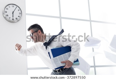 Stressed anxious businessman in a hurry checking time and running, he is late for his business appointment ストックフォト ©