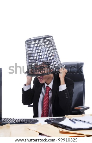 Stressed asian businessman covering his head with rubbish bin