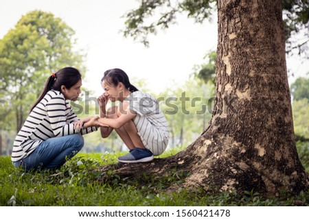 Stressed asian child girl sitting crying and thinking about problems at park,sad female teenage having psychological trouble with depressive symptoms feel despair,depression, sorrow,mental disorder