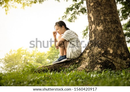 Stressed asian child girl was sitting alone crying under the tree at park,desperate female teenage with depressive symptoms feel sad grieving weeping suffering from anxiety,depression disease concept