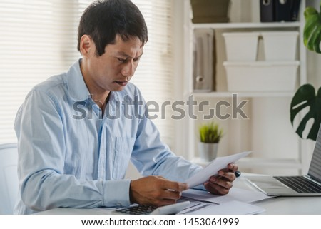 Stressed asian young man looking at credit card bills and worrying about his expense.