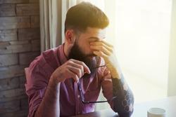 Stressed bearded man in glasses making break