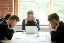 Stressed boss and executive team searching problem solution at meeting, partners holding heads in hands depressed by failure bad news, feeling desperate about company bankruptcy or financial crisis