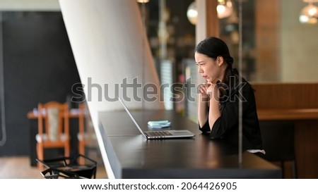 Stressed business female entrepreneur focused and concentrated on online business consulting via laptop computer.