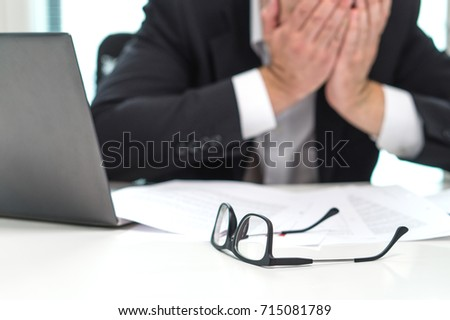 Stressed business man covering face with hands in office. Working over time or too much. Problem with failing business or confusion with crisis. Entrepreneur in bankruptcy. Burnout and overwork.