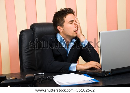 Stressed business man with problems on laptop holding  face in his hand