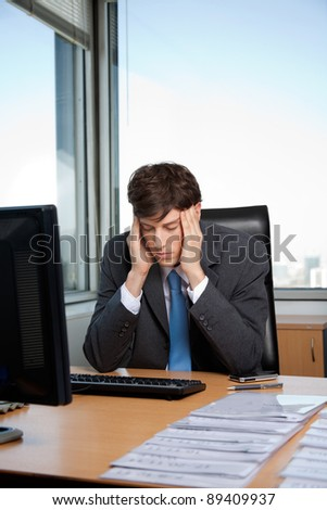 Stressed business manager sitting at his desk