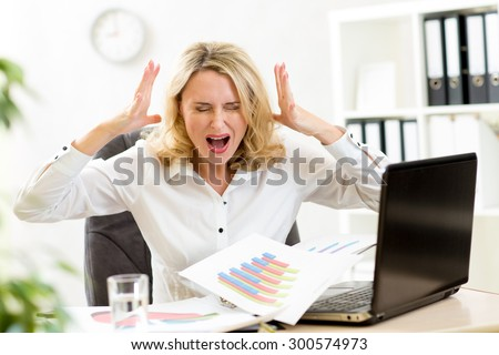 Stressed business woman at laptop in office
