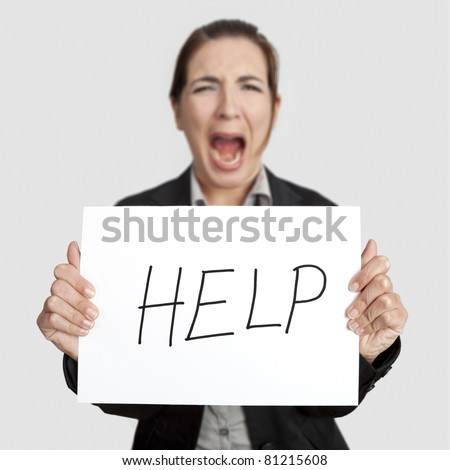 """Stressed business woman imploring for help, holding a cardboard with the message """"Help"""". Focus is on the cardboard"""