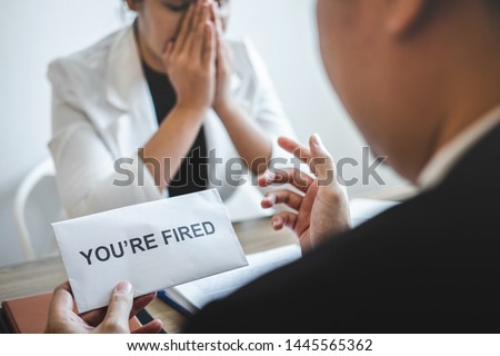 Stressed business woman receive fired letter from employer and packing belongings and files into brown cardboard box, changing and resigning from work concept.